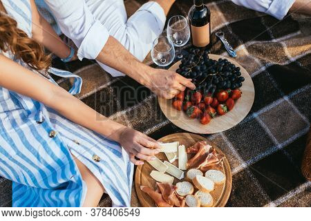 Partial View Of Couple Near Fruits, Soft Cheese And Glasses On Plaid Blanket