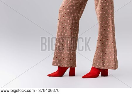 Partial View Of Stylish Woman In Beige Trousers And Red Boots On Grey