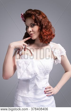 Cute And Positive Smiling Redhaired Caucasian Female Posing In White Wedding Dress And Little Purse