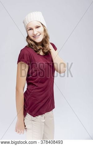 Portrait Of Caucasian Teenager Girl With Teeth Brackets. Posing With Backpack Indoors.