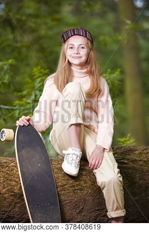 Teenager Concepts. Portrait Of Happy Smiling Caucasian Teenage Girl Posing With Longboard Skate Outd