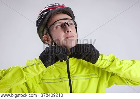 Cycling Concepts. Portrait Of Young Caucasian Man In Cycling Outfit. Putting On Protective Helmet. H