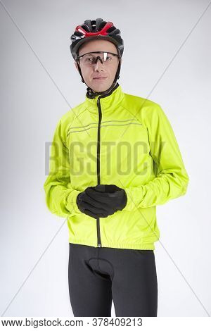 Cycling Concepts. Portrait Of Young Caucasian Man In Cycling Outfit. Putting On Protective Helmet.ve