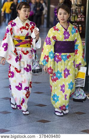Kyoto, Japan - November, 8, 2019: Two Beautiful Japanese Geishas In Floral Silk Kimono In Traditiona