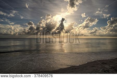 Sun Peeks Through The Clouds Over The Ocean At Sunset In Naples, Florida