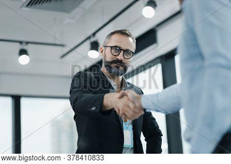 Businessmen Making Handshake In Meeting Room, Congratulation.