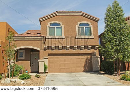 New Two-story, Tan And Orange Terra Cotta Stucco Home In Tucson, Arizona, Usa With Beautiful Blue Sk