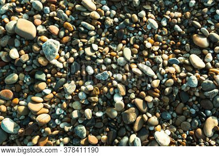 Ocean beach sand with pebbles texture.