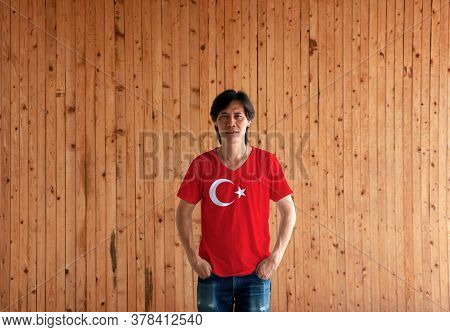 Man Wearing Turkey Flag Color Shirt And Standing With Two Hands In Pant Pockets On The Wooden Wall B