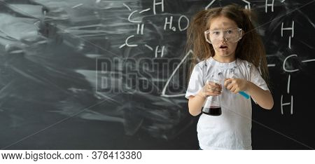 Little Girl Makes Experiments In Chemistry Lesson. Explosion During The Experiment. . Place For Text