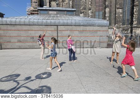 Cologne, Germany - July 07, 2018: Children Catching Soap Bubbles In The Street Near Of The Cologne C