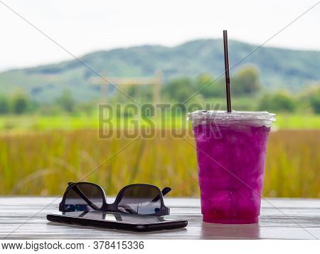 Side View Of Sunglasses, Smartphone And Herb Purple Water Or Flower Butterfly Pea Water On White Woo
