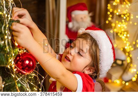Beautiful Woman Decorating Christmas Tree With Bauble - New Year Tradition. Christmas Child Decorati