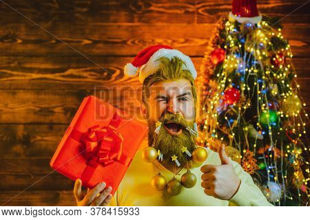 Funny Santa. Happy Santa Dressed In Winter Clothing Think About Christmas Near Christmas Tree. Theme