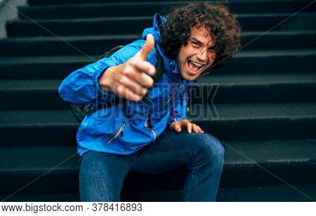 Cheerful Smiling Young Man With Curly Hair Sitting On Stairs Of A Building With Backpack, Showing Th