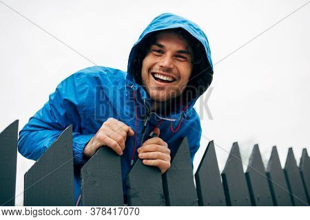 Man Smiling Broadly And Wearing Blue Raincoat During Rain Outside. Handsome Male In Blue Raincoat En