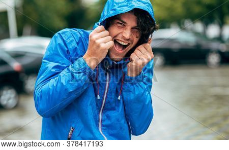 Happy Man Laughing And Wearing Blue Raincoat During The Rain Outside. Handsome Male In Blue Raincoat