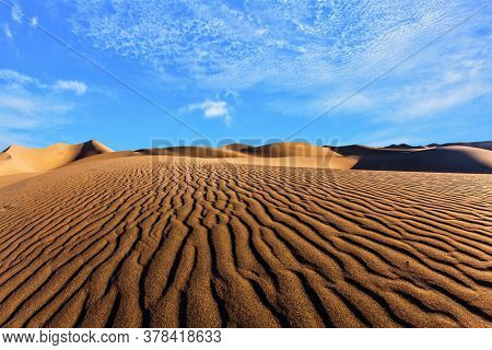 Magic play of light on the sand. Dunes illuminated by orange sunrise. USA. Mesquite Flat Sand Dunes is part of Death Valley in California. The concept of active, ecological and photo tourism