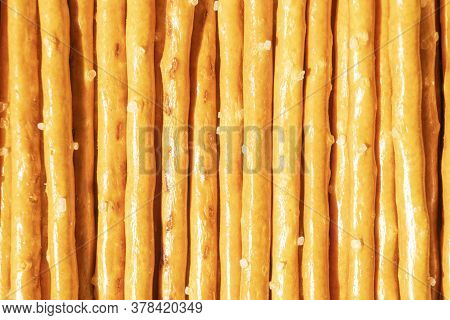 Salty Sticks Line In Row Background. Top View. Snack Texture Background. Salty Bread Sticks For Beer