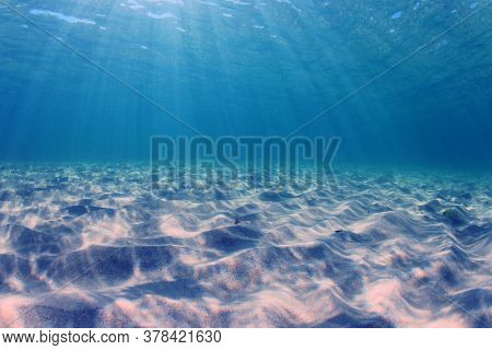Underwater blue ocean background over sandy sea bottom. Sunlight in clear blue water