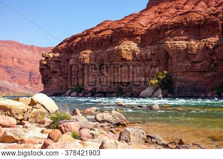 Stormy wide river with rapids and steep banks of red sandstone and cold water. Lee's Ferry is a historic boat ferry across the Colorado River. USA. The concept of active and photo tourism