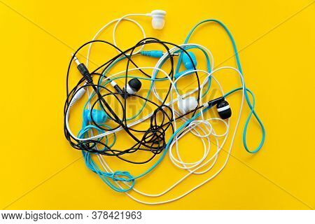 Bunch Of Different Earphones Isolated On Yellow Background. Color Conceptual. Conceptual Minimalism.