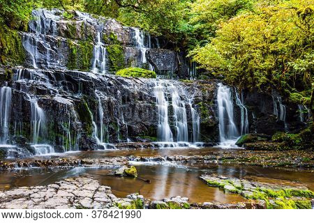 South Island, New Zealand. Southern Scenic Route Waterfalls. Picturesque multi-tiered cascading waterfalls among the green forest. Purakaunui Falls. The concept of active and photo tourism