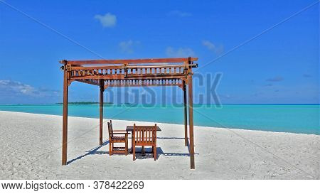 Relax On The Maldives Beach. There Is A Canopy On The White Sand, With A Wooden Table And Chairs Und