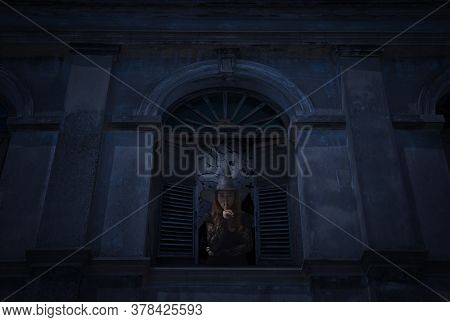 Halloween Witch Showing Silence Sign With Finger Standing In Old Damaged Window With Wall Over Cross