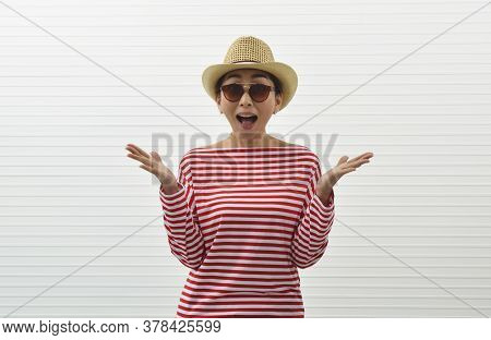 Surprised Young Asian Woman Wearing Red Stripped Shirt, Sunglasses And Straw Hat Standing Over White