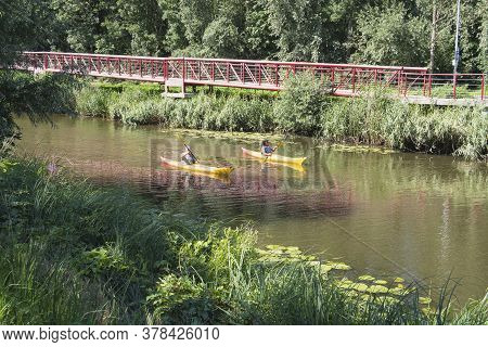 Lokeren, Belgium, July 13, 2020, Man And Woman Are Sailing On The Durme In A Yellow Canoe
