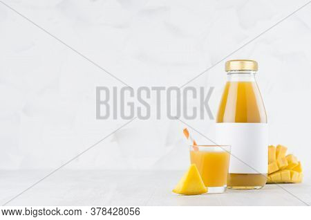 Fresh Yellow Mango Juice In Glass Bottle Mock Up With Blank Label, Straw, Wine Glass, Fruit Pieces O