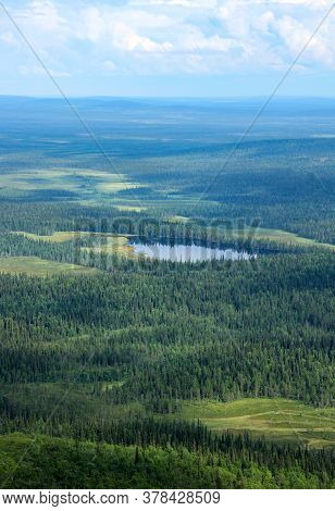 Northern Wilderness With Green Forests, Swamps And Blue Lake, White Clouds Sky