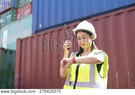 Young Asian Woman In Safety Uniform Hand Taking Walkie Talkie And Looking Watch At The Container Dep
