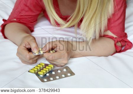 Woman With Pills, Female Hands On A Bed With A Blister Pack Of Tablets. Blonde Girl Taking Medicatio