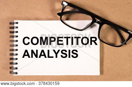 Competitor Analysis. Inscription On A White Sheet Of Notebook Near A White Pen And Pieces Of Paper