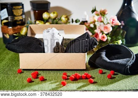 Several Pairs Of New Male Cotton Socks With A Brown Cardboard Box On A Green Surface And Flowers Bac
