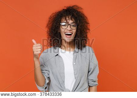 Smiling Young African American Woman Girl In Gray Casual Clothes, Eyeglasses Isolated On Orange Back