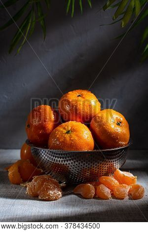 Fresh Juicy Tangerines With Drops Of Water In A Metal Colander And Peeled Tangerine Slices Lie Side