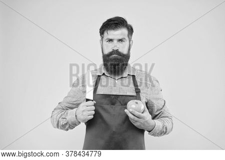 Brutal Cook Cut Tomato. Man In Apron With Long Beard. Handsome Confident Guy Cooking Vegetable Food.