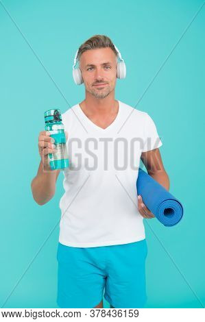 Muscular Man Exercising At Home With Sport Mat, Gym Playlist Concept.