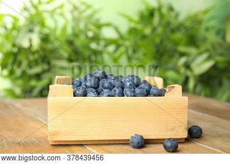 Tasty Ripe Blueberries In Crate On Wooden Table