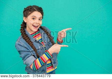 For Your Attention. Happy Girl Pointing Index Fingers At Blue Background. Little Kid With Pointing G
