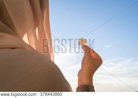 One Piece Of A Puzzle In Muslim Women Hands On Sunset Blue Sky Background. Man And Woman. Relationsh