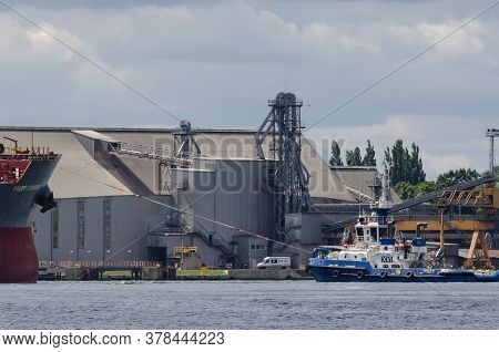 Swinoujscie, West Pomeranian / Poland - 2020: Tugboat Helps  Vessel Move Away From Transshipment Ter