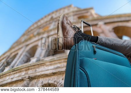 Young Man Is Relaxing In Rome And Has Legs On Suitcase. Colosseum In Background.