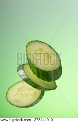 Pieces Of Cucumber With A Snous Fall On A Green Background With A Gradient.