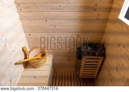 Sauna Room. Empty Wooden Steam Room With Stone Heater.sauna Room For Good Health. Sauna Room With Tr