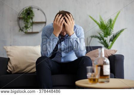 Alcoholism, Depression, Crisis And Bankruptcy Concept - Depressed Businessman Drinking Alcohol At Ho