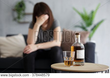 Female Alcoholism And Depression Concept - Young Woman Crying And Drinking Alcohol At Home